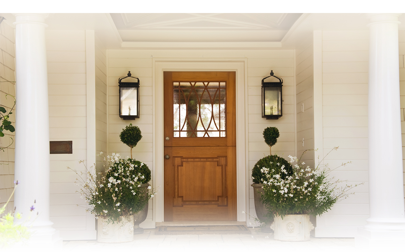 View of front porch and front door with plants on either side of the door.